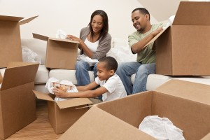 Family of three packing belongings into boxes